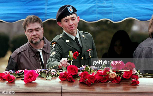 A soldier places a flower on the casket of Sgt Jessica Housby February 19 2005 in Rock Island Illinois Sgt Housby of the Army National Guard's 1644th...