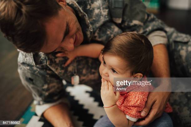 US soldier playing with his daughter