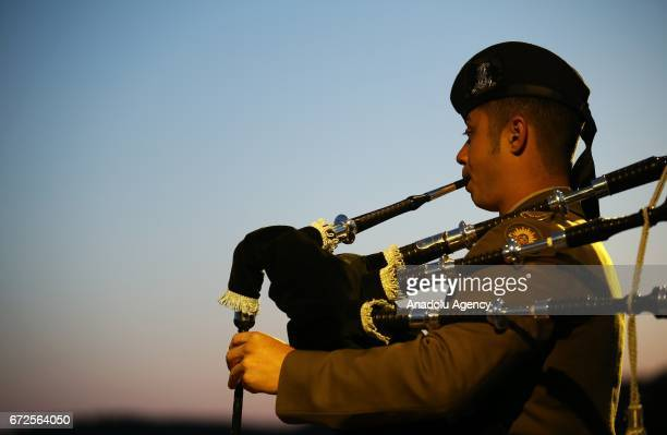 A soldier plays bagpipes as people wrap themselves with sleeping bag and thermal blankets during the ANZAC Dawn service in Canakkale Turkey on April...