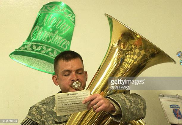 Soldier plays Christmas carols at a Christmas lunch at Bagram Air Base, some 50 kms north of Kabul, 25 December 2006. Many soldiers were able to call...