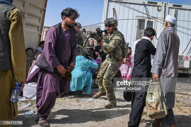 Soldier point his gun towards an Afghan passenger at the Kabul airport in Kabul on August 16 after a stunningly swift end to Afghanistan's 20-year...