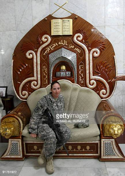 A US soldier poses for a picture as she sits on a chair that belonged to executed Iraqi dictator Saddam Hussein at the former presidential palace...