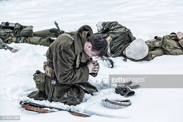 wwii soldier praying for ambushed comrade war casualties - soldier praying stock photos and pictures