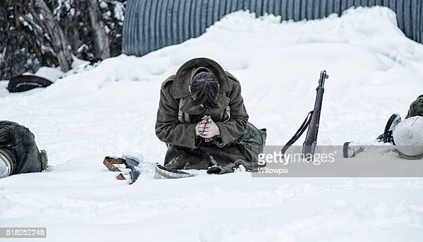 wwii soldier praying for dead war casualties - soldier praying stock photos and pictures
