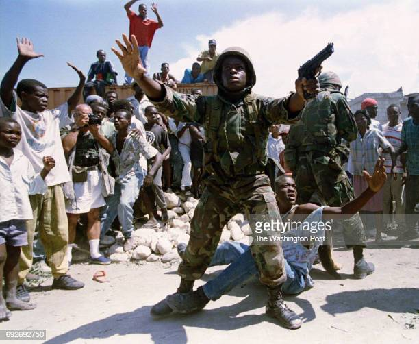 S Soldier protects a suspect from the crowd after a explosive device was thrown into a proAristide march on September 29 1994 in PortauPrince Haiti...