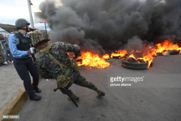 A soldier pulls a burning tyre away from the street during clashes following a protest against alleged electoral fraud in Tegucigalpa Honduras 15...