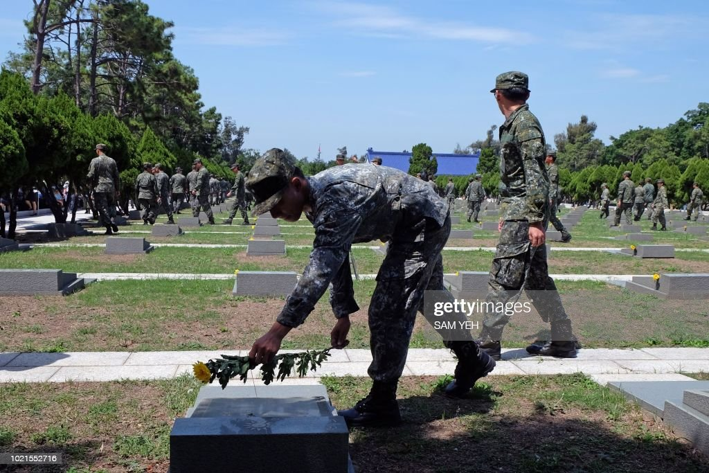 A soldier puts a flower on a grave in a cemetery for soldiers during the 60th anniversary of the '823 bombardment' in Kinmen on August 23, 2018. - The tiny Taiwanese island of Kinmen on August 23 marked the 60th anniversary of a Chinese artillery attack that killed hundreds of people, as cross-strait tensions rise once more.
