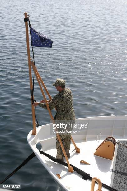 A soldier raises a flag on the bow of a ship at Hamad Port in Doha Qatar on June 16 2017 After 12 billion dollars worth F35 fighter jet agreement...