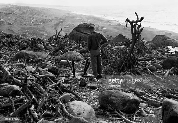 A soldier relieves himself as he stands on a hilltop overlooking the devastation wreaked during the Battle of Iwo Jima one of the fiercest battles of...