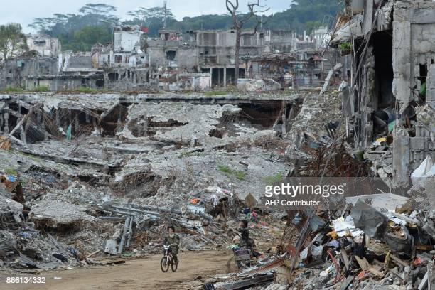 A soldier rides a bicycle past bombedout buildings in what was the main battle area in Marawi on the southern island of Mindanao on October 25 days...