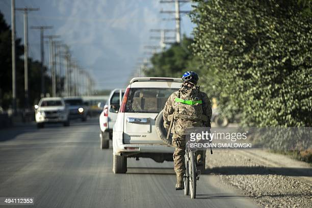 A US soldier rides a bike along roads at Bagram Airfield in Parwan on May 27 2014 US forces will complete their withdrawal from Afghanistan by the...