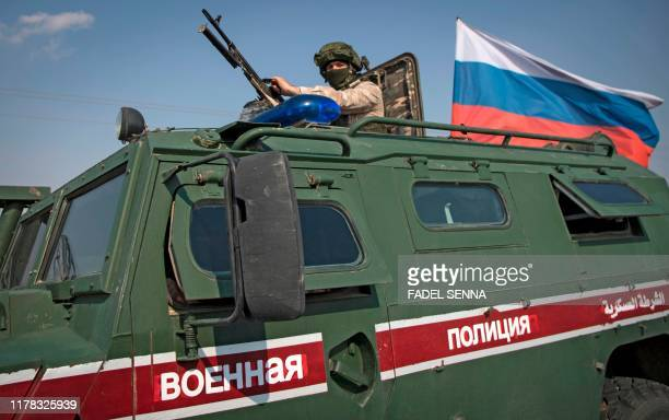 Soldier rides atop a Russian military vehicle near the Syrian northeastern city of Qamishli on October 26, 2019. - Turkey and Russia struck a deal in...