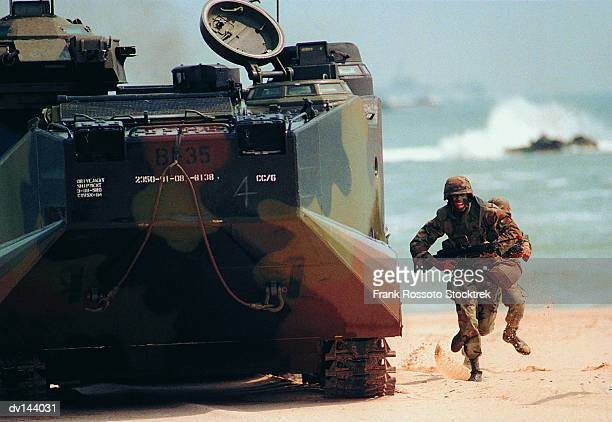 soldier running beside tank on beach - marines military stock photos and pictures