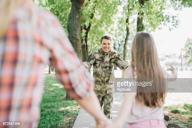 soldier running towards his family - civilian stock pictures, royalty-free photos & images