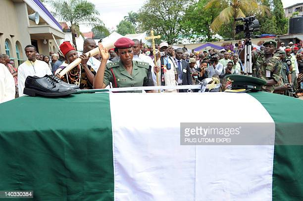 A soldier salutes after arranging the boots and cap on the casket of Nigeria's secessionist leader Odumegwu Ojukwu during his funeral at his native...