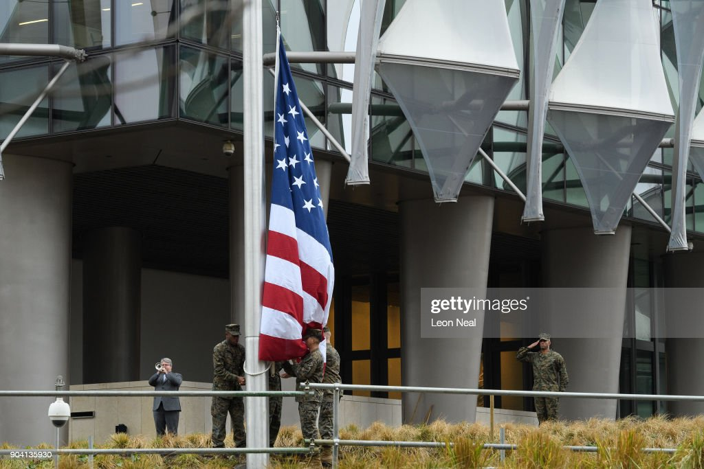 A soldier salutes and a man plays the 'Star Spangled Banner' as soldiers raise the American flag at the new US embassy for the first time on January 12, 2018 in London, England. President Trump has tweeted that he will not go ahead with his planned visit to the new billion-dollar embassy, blaming previous President Barack Obama's 'bad' embassy deal as his reason for cancelling. Critics have speculated that Mr Trump could have been wary of protests and demonstrations if he chose to go ahead with his February visit.