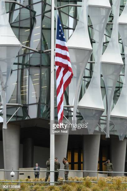 A soldier salutes and a man plays the 'Star Spangled Banner' as soldiers raise the American flag at the new US embassy for the first time on January...