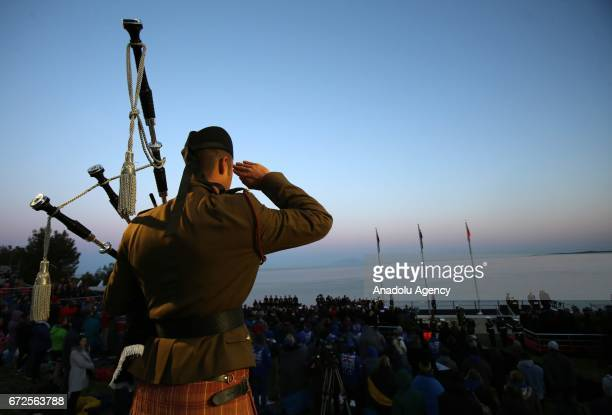 A soldier salutes to people who wrap themselves with sleeping bag and thermal blankets during the ANZAC Dawn service in Canakkale Turkey on April 25...