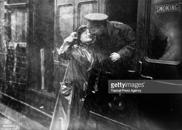 A soldier saying goodbye to a loved one in the rain at Victoria station London as he leaves for the front