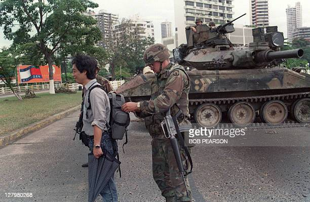 A US soldier searches the pack of a Papal courier during Operation Just Cause on December 28 1989 outside the Vatican embassy in Panama City US...