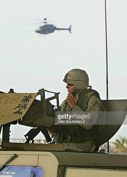 US soldier secures the road where a US military convoy was attacked by an improvised explosive device as a US military helicopter hovers over the...