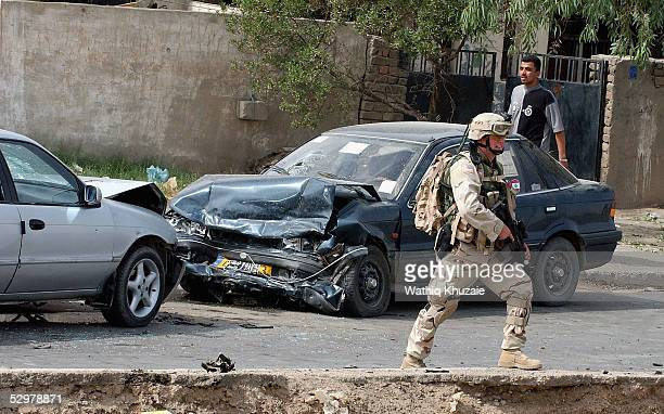 S soldier secures the scene of a suicide car bomb explosion which failed to hit a US military convoy May 25 2005 in the area south of Baghdad Iraq...