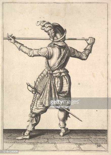 A soldier seen from the rear while turning to the right and holding his pike horizontally from the Lansquenets series plate 30 in Wapenhandelinghe...