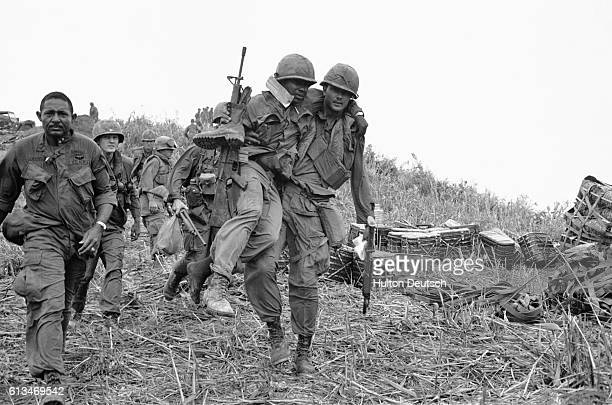 A US soldier serving in Vietnam carries a wounded comrade down Hill Timothy