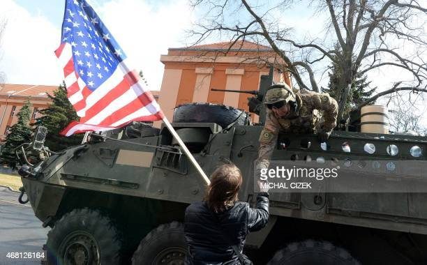 A US soldier shakes hands with a boy holding a US national flag as US military convoy arrives to Czech army barracks on March 30 2015 in Prague after...