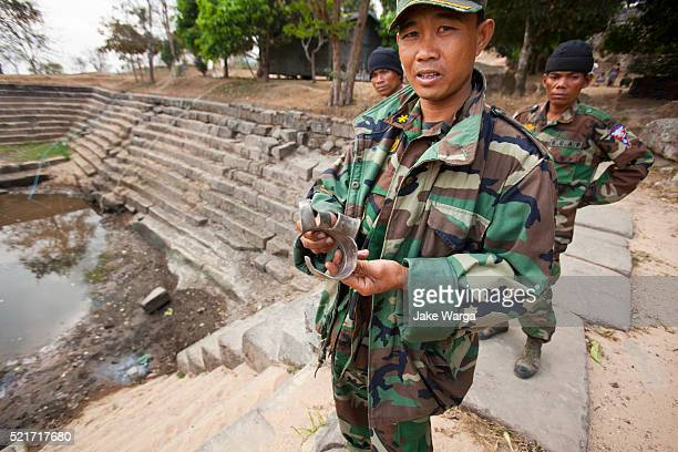 soldier showing shell that killed his brother, also a soldier, days earlier, preah vihear temple, cambodia - jake warga stock pictures, royalty-free photos & images