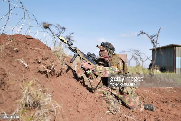 A soldier shuffles back to position to fire his machine gun during a simulated military excercise of the British Army Training Unit in Kenya together...