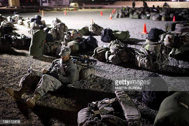 A US soldier sits amid backpacks as he waits to head home on December 19 2011 at Camp Virginia in the Gulf emirate of Kuwait after crossing from Iraq...
