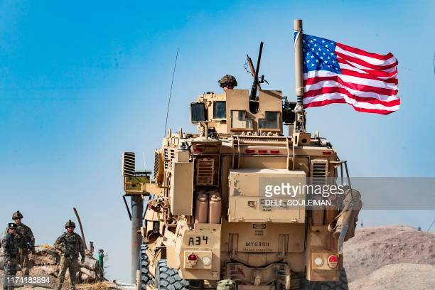 A US soldier sits atop an armoured vehicle during a demonstration by Syrian Kurds against Turkish threats at a USled international coalition base on...