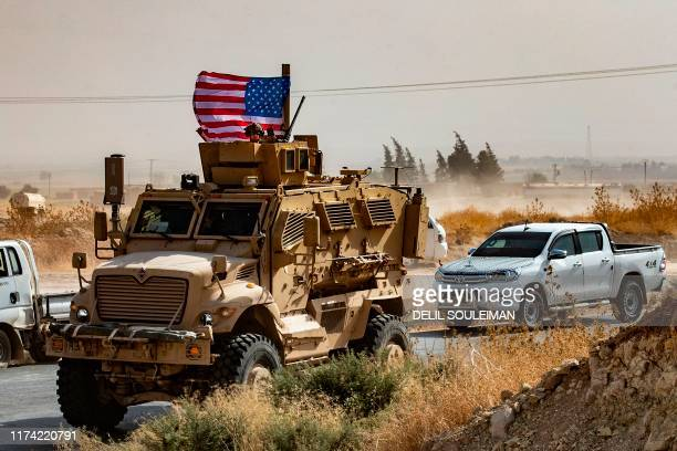 Soldier sits atop an armoured vehicle during a demonstration by Syrian Kurds against Turkish threats next to a base for the US-led international...