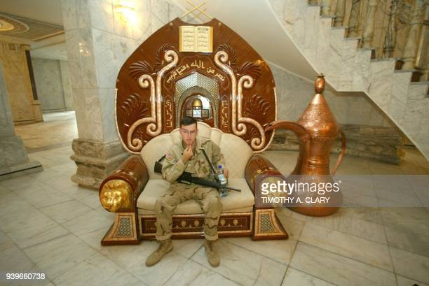 A US soldier sits in a seat at the Radwaniyah Palace used during the toppled regime of Iraqi leader Saddam Hussein as a reception palace for guests...