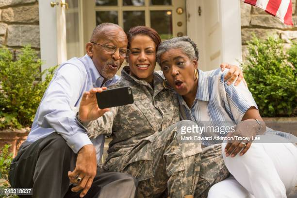 Soldier sitting on front stoop with parents and posing for cell phone selfie