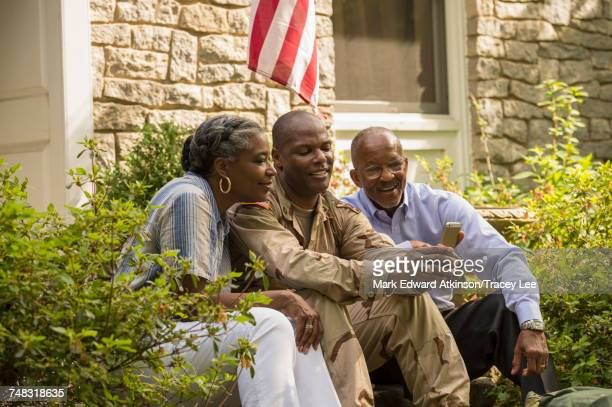 Soldier sitting on front stoop with parents and texting on cell phone
