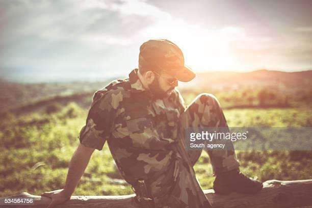 Soldat assis sur clôture en bois