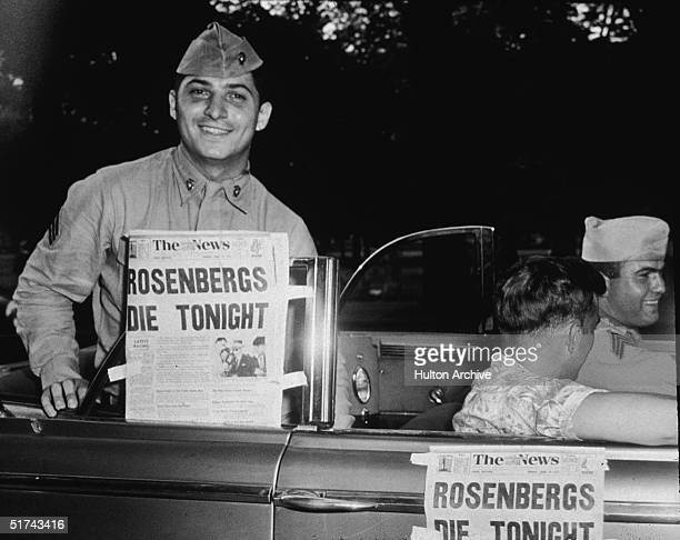 A soldier smiles from the backseat of a convertible as he proudly displays a newspaper announcing the impending executions of Julius and Ethel...
