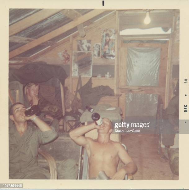 Soldier smokes a cigarette and his colleagues tilt their heads back to lift bottles of alcohol to their mouths while sitting in a cramped wooden...