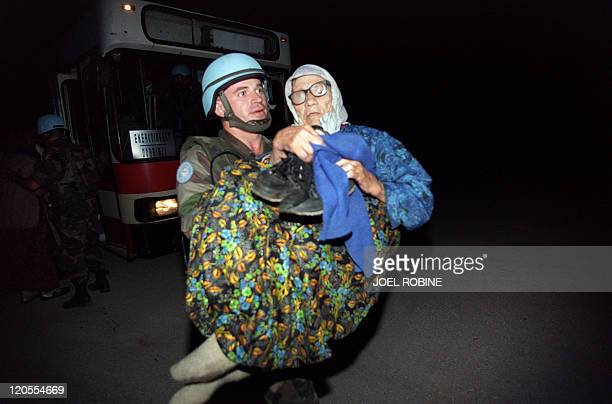 Soldier soldier carries a wounded elderly woman upon her arrival to the frontline crossing point close to the government held town of Klandanj on...