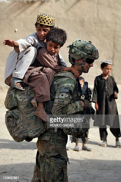 US soldier Specialist Collin Rand from the Charlie Company 287 Infantry 3rd Brigade Combat Team plays with Afghan children during a joint patrol with...