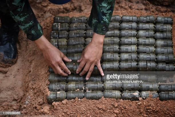 TOPSHOT A soldier stacks antipersonnel mines before a controlled detonation at the official Destruction Ceremony of Thailands Retained AntiPersonnel...