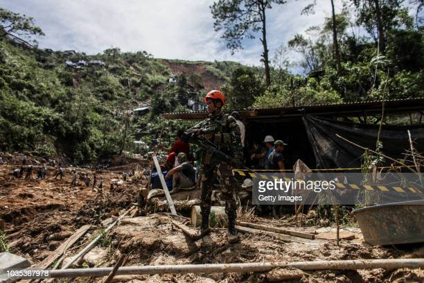 A soldier stand guard as rescuers dig at the site where people were believed to have been buried by a landslide on September 18 2018 in in Itogon...
