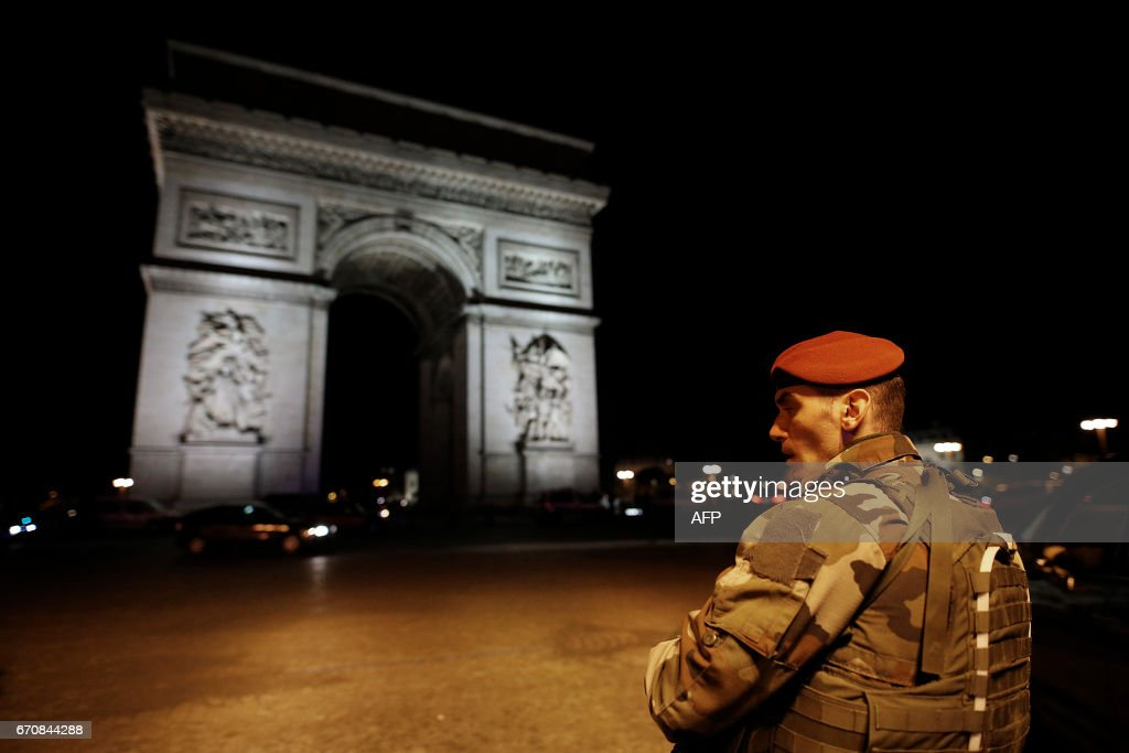TOPSHOT - A soldier stand guards near the Arc de Triomphe after a shooting at the Champs Elysees in Paris on April 20, 2017. One police officer was killed and another wounded today in a shooting on Paris's Champs Elysees, police said just days ahead of France's presidential election. France's interior ministry said the attacker was killed in the incident on the world famous boulevard that is popular with tourists. PHOTO / Benjamin Cremel