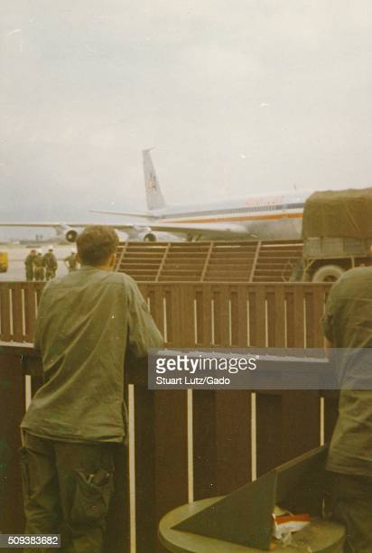 Soldier standing behind a wood fence looking at an American Airlines plane and other soldiers on the tarmac Danang Airport Vietnam 1964