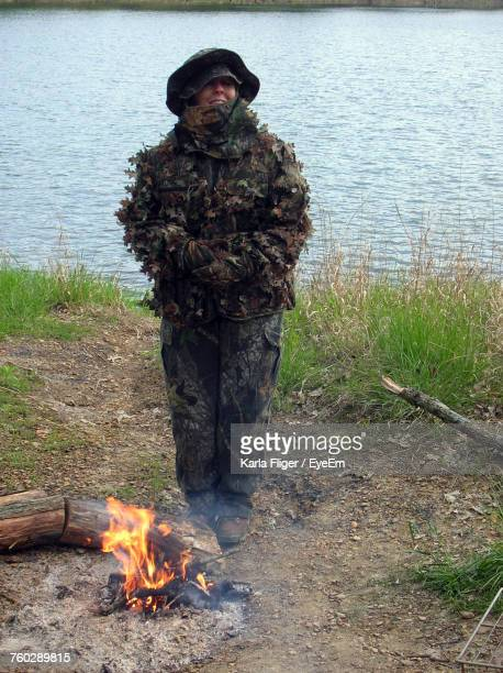 Soldier Standing By Bonfire Against River