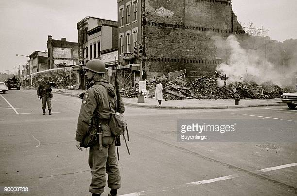 soldier standing guard in a Washington DC street with the ruins of buildings that were destroyed during the riots that followed the assassination of...