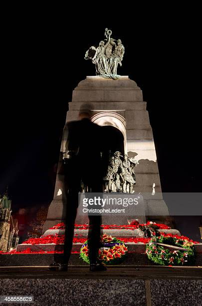 Soldier standing in front of Remembrance Day Memorial