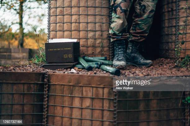 soldier standing on hesco barriers next to parachute flares in green tubes at a sentry box - army stock pictures, royalty-free photos & images